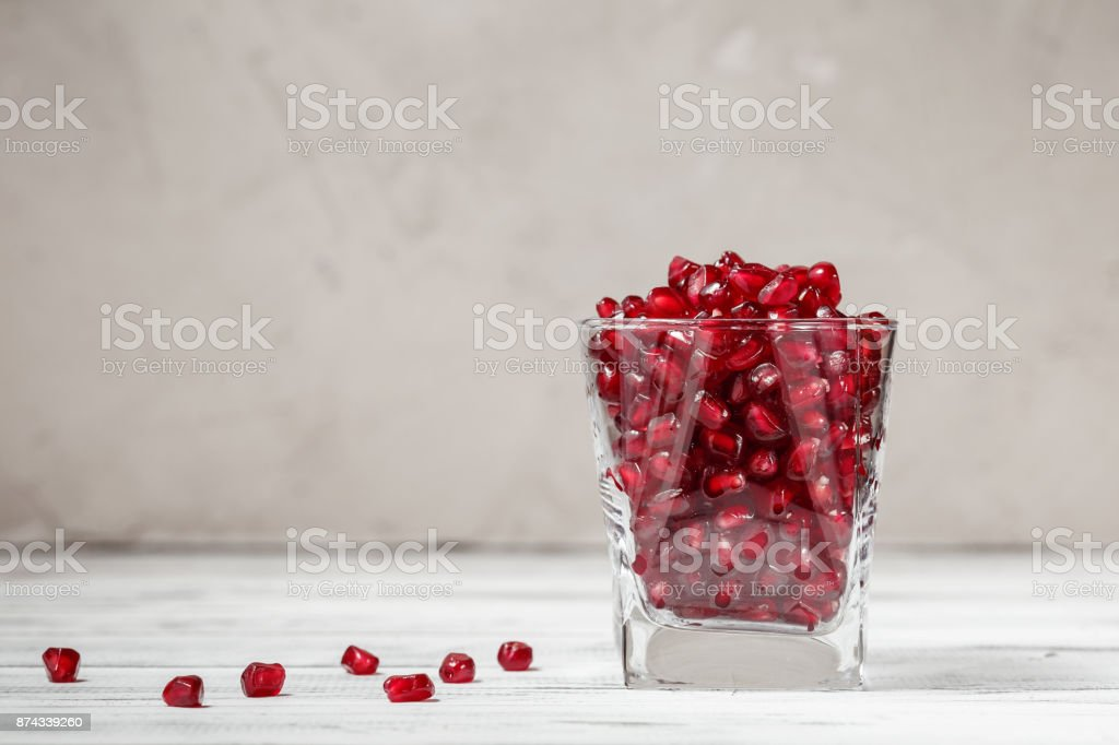Glass filled with pomegranate seeds on the table stock photo