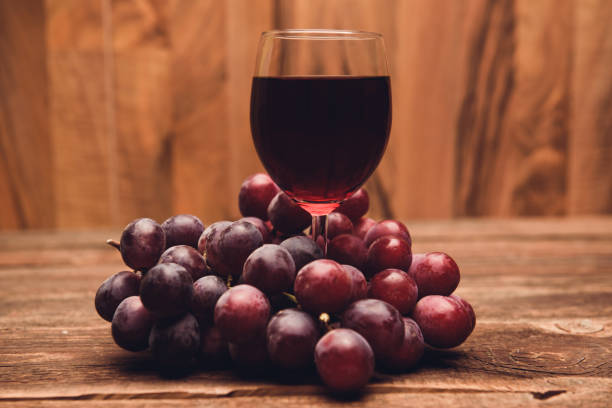 Glas gefüllt mit rotem Traubensaft oder Wein und Früchten – Foto