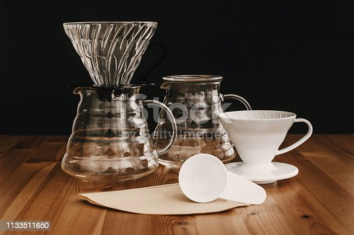 istock Glass flask, paper filters, glass and ceramic dripper, spoon for pour-over coffee. Alternative coffee brewing method. Stylish accessories and items for alternative coffee on wooden table 1133511650