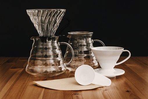 Glass flask, paper filters, glass and ceramic dripper, spoon for pour-over coffee. Alternative coffee brewing method. Stylish accessories and items for alternative coffee on wooden table