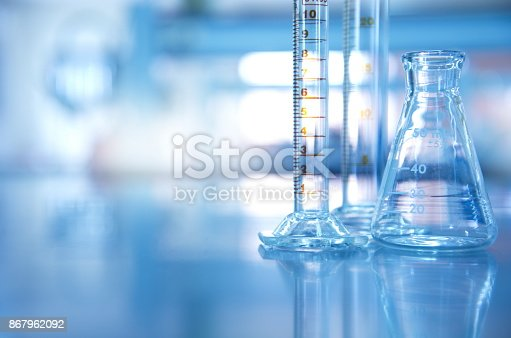 istock glass flask with cylinder in blue science laboratory background 867962092