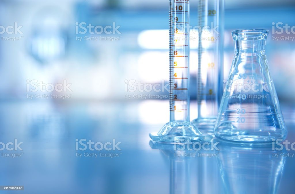 glass flask with cylinder in blue science laboratory background stock photo