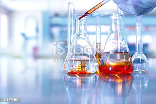 891126112istockphoto glass flask with hand of scientist drop orange solution in blue chemistry science research laboratory background 921472532