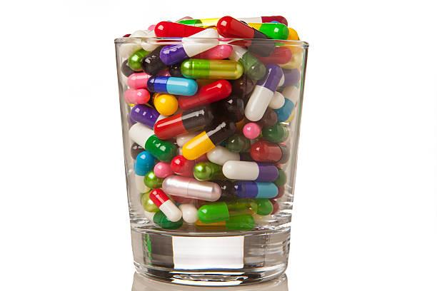 Glass full of capsules and pills stock photo