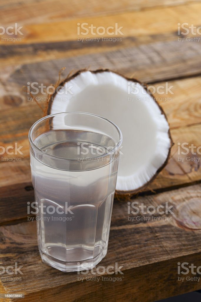 Glass full of coconut water and open coconut on wooden table royalty-free stock photo