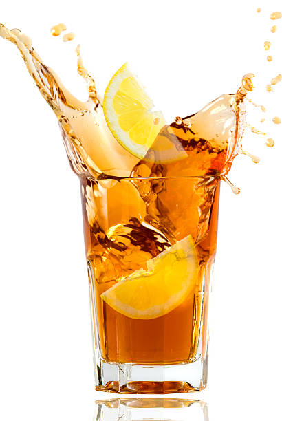 Glass full of fresh iced tea with lemon in artistic splash stock photo