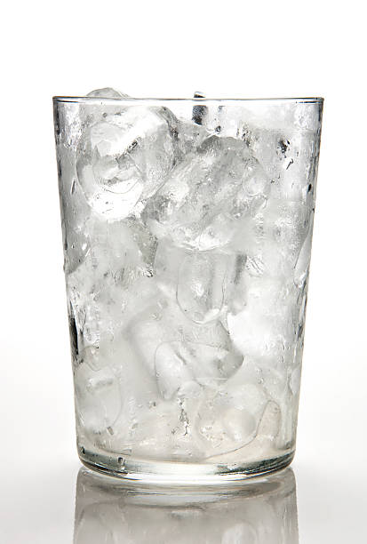 Glass full of ice cubes against a white background stock photo