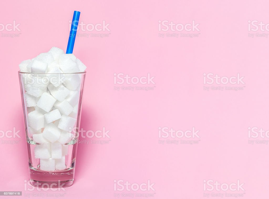 Glass full of sugar cubes - unhealthy diet concept. stock photo