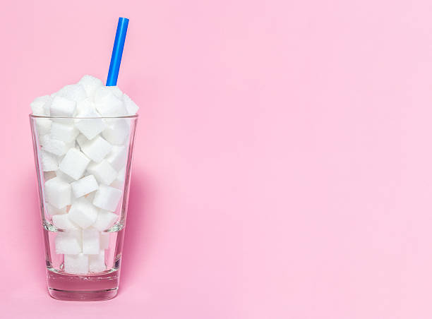 glass full of sugar cubes - unhealthy diet concept. - soda pop stock photos and pictures