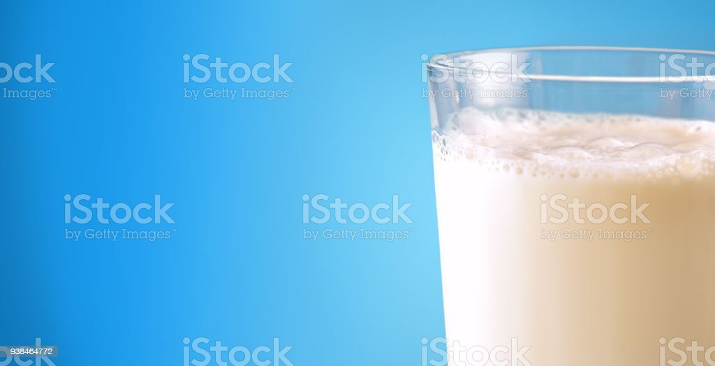 Glass full with milk on blue gradient isolated background stock photo