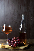 A glass glass with rose wine next to a bottle and grapes on a wooden stand. Vertical orientation. Copy space.