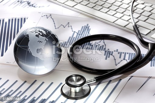 Business concept. Glass globe and stethoscope on paper background with stock chart  and keyboard