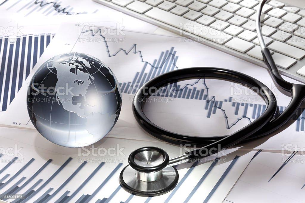 Glass globe and stethoscope on stock chart stock photo