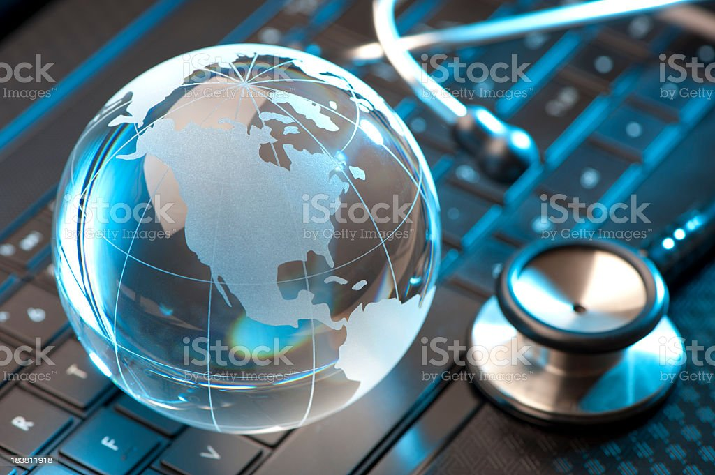 Glass globe and stethoscope stock photo