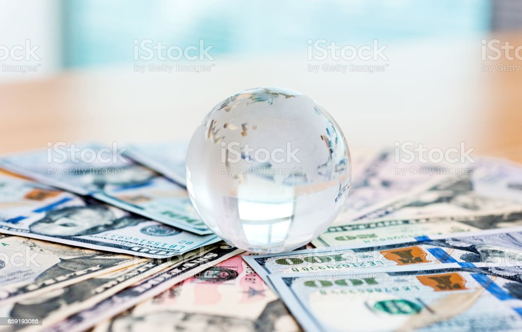 Glass globe and US dollar bills foto stock royalty-free