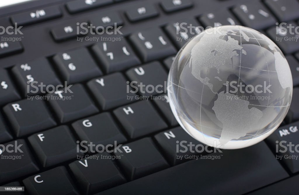 Glass globe on computer keyboard royalty-free stock photo