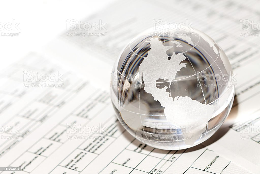 Glass globe paperweight on top of chart paperwork stock photo