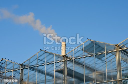 Glass  greenhouse with smoking  pipe emitting  smoke against blue sky . Heating the greenhouses in winter  .Environmental pollution.