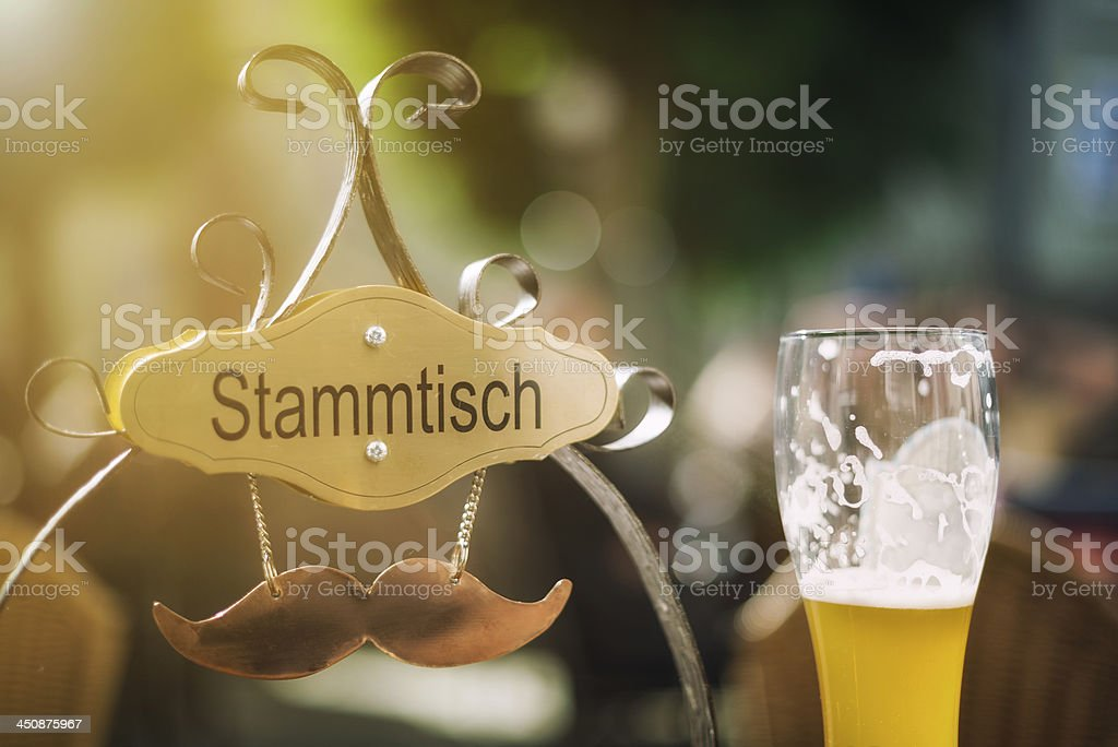 Glass half full of beer next to hanging metal moustache stock photo