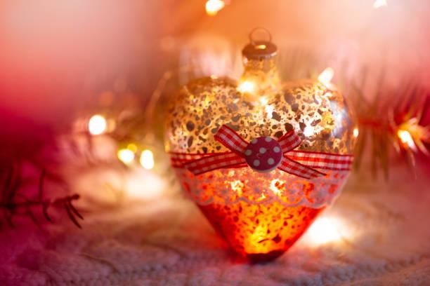 glas heart, weihnachtsspielzeug - ein kranz in den händen auf dem hintergrund der eine warme strickpullover, umgeben von fichten filialen in rottönen gehalten. abendzeit. - weihnachtsspende stock-fotos und bilder