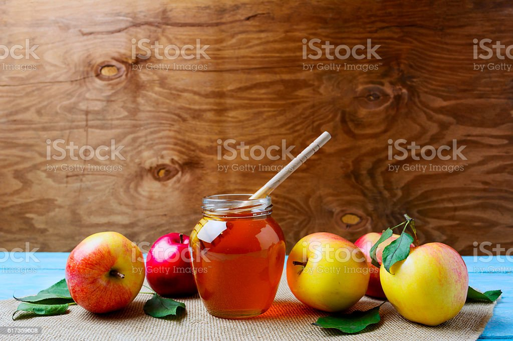Glass honey jar with dipper and fresh apples, copy space stock photo