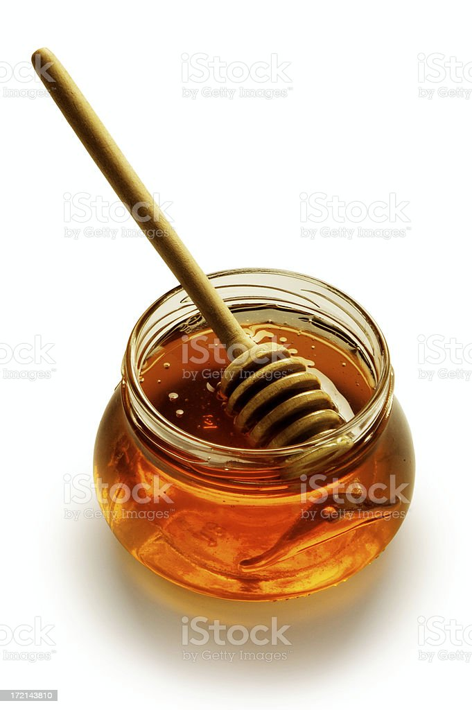 Glass honey pot with stick isolated on white background stock photo