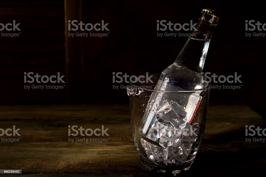 Glass ice bucket with a bottle of tonic, rum or other alcohol on dark wooden backgorund stock photo