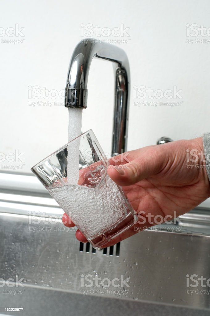 Glass is filled with fresh water from a faucet royalty-free stock photo