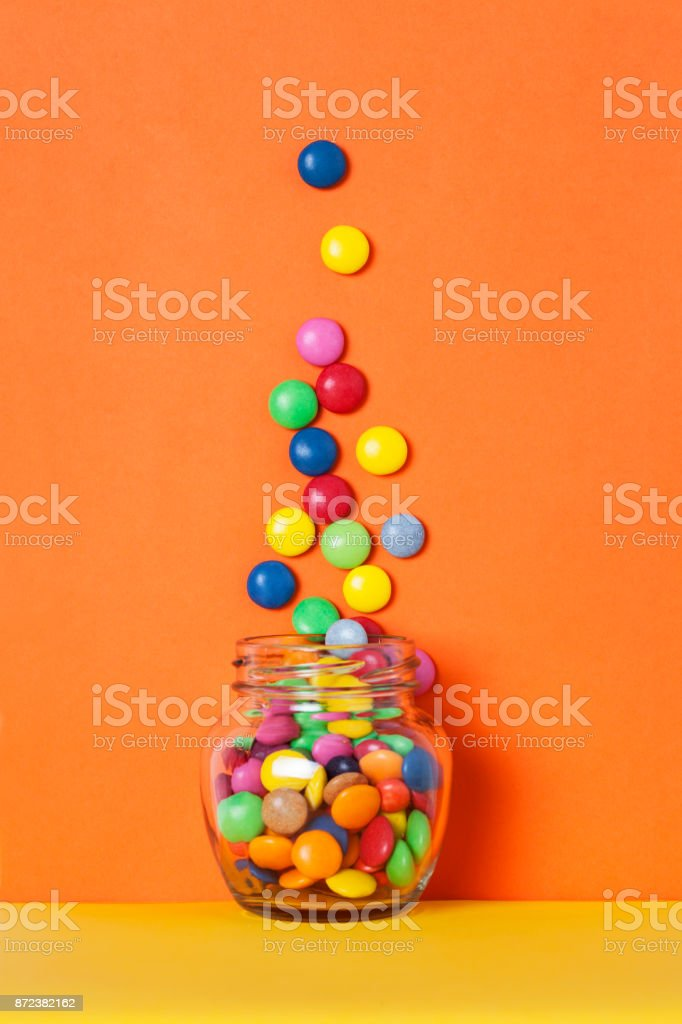 Glass jar and heap colorful candy stock photo
