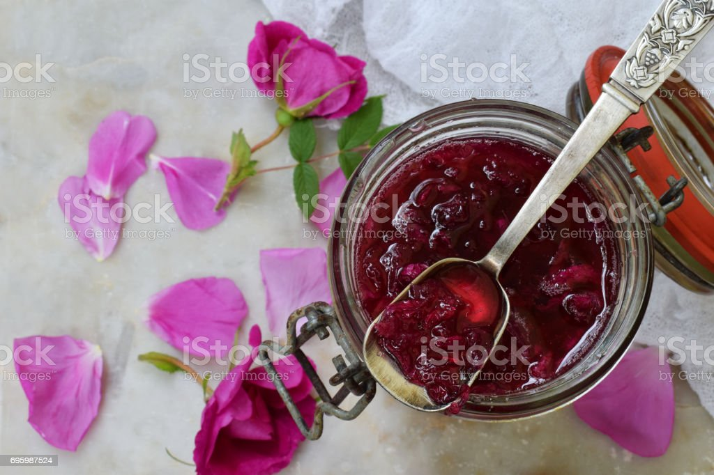 Glass jar and little spoon with tea rose petal jam on light marble background. Copy space for text. stock photo