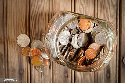 Glass jar filled with USA coins against rustic wood panel background with rusty nail heads showing