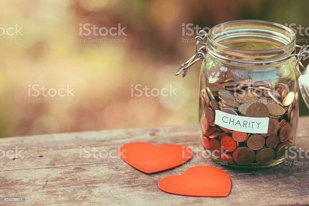 Glass jar for charity and two heart shapes stock photo