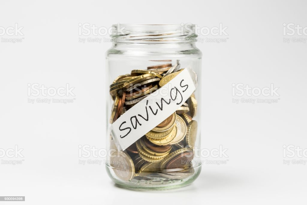 Glass jar full of coins on white background stock photo