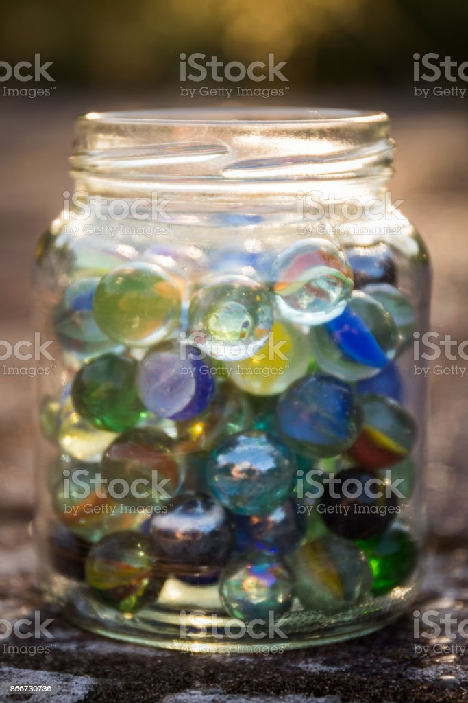 Glass jar full of colored marbles against a background of a setting sun. stock photo