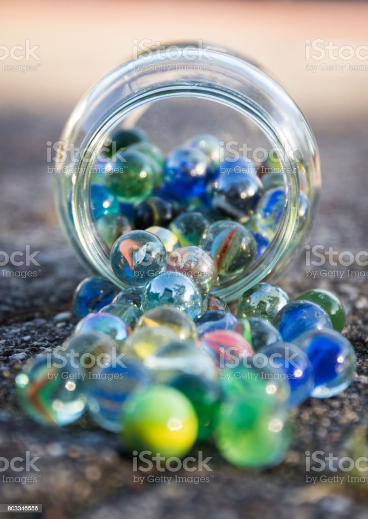 Glass jar full of crushers, fallen on the street. Front view of jar. stock photo