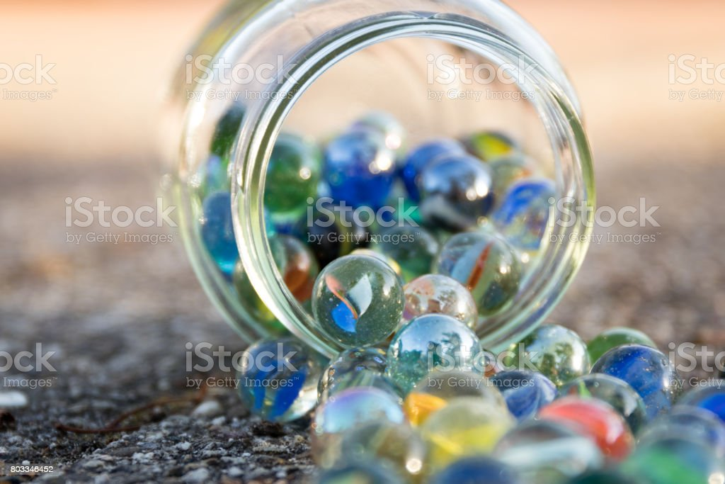 Glass jar full of crushers, fallen on the street. View of jar at an angle. stock photo