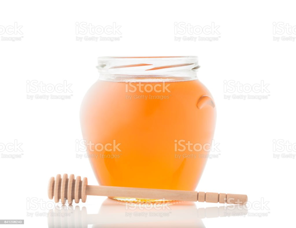 Glass jar full of honey and wooden stick on it isolated on a white background stock photo