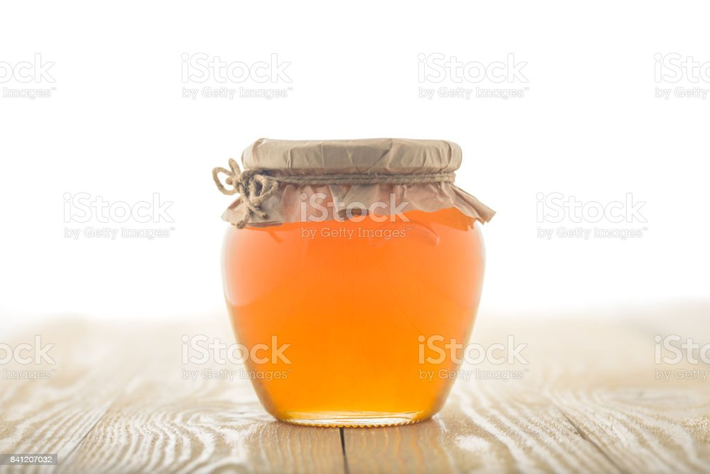Glass jar full of honey and wooden stick on it isolated on a wooden background stock photo