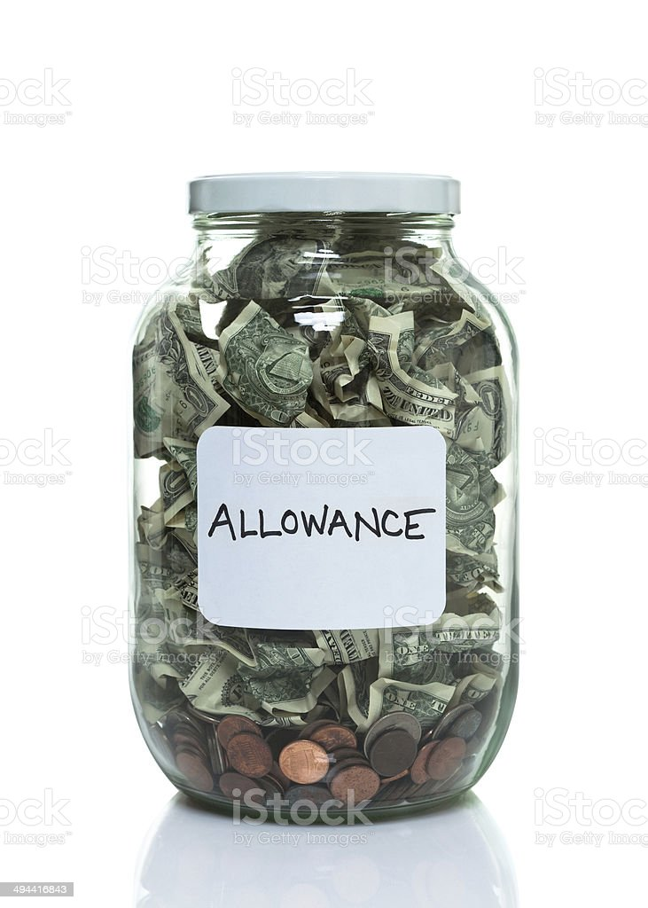 Glass jar full of money with a white allowance label stock photo