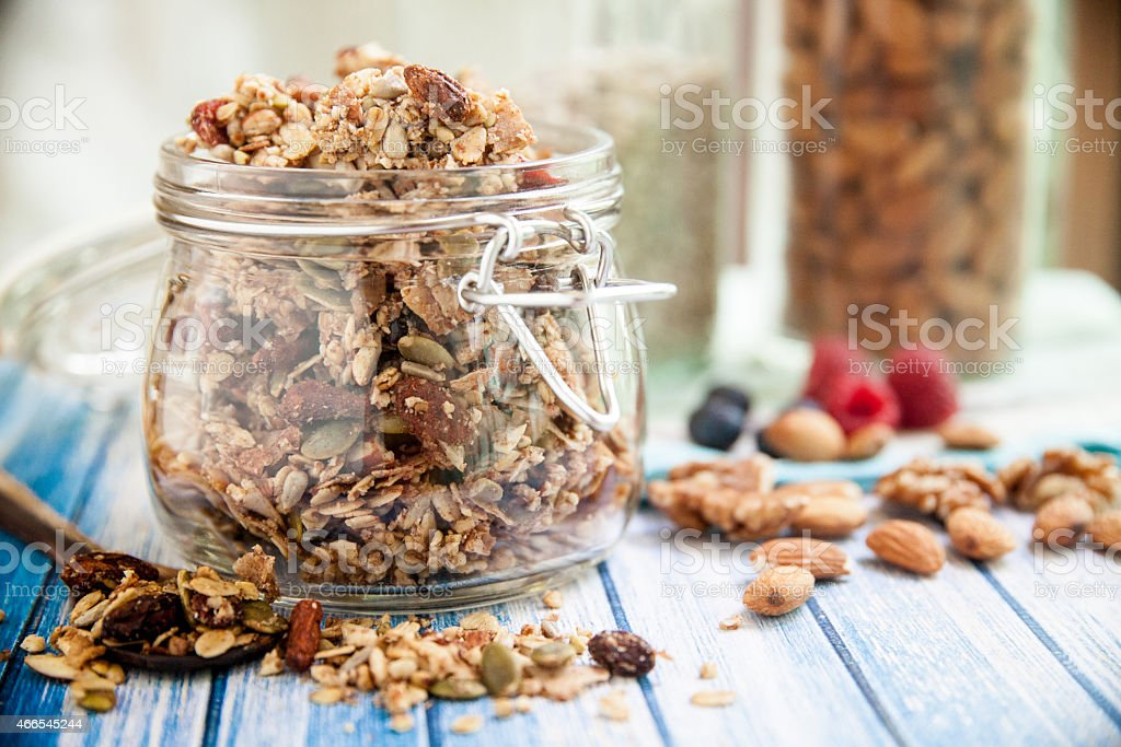 A glass jar in a blue wooden table overfilled with granola  stock photo