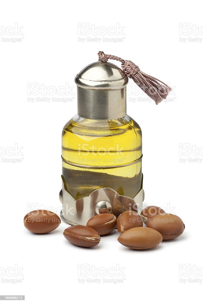 A glass jar of Argan oil with nuts on the side stock photo