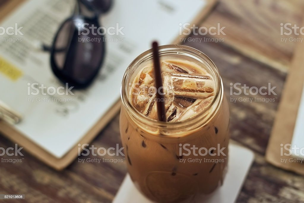 Glass jar of chocolate milk with ice on table stock photo