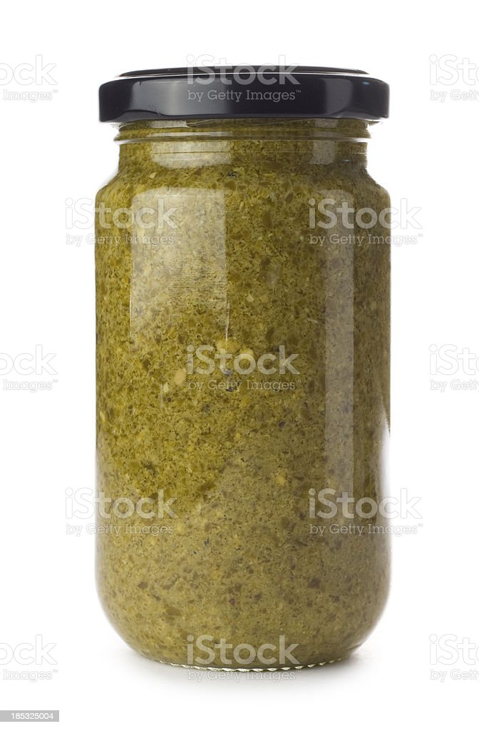 Glass jar of green pesto on a white background royalty-free stock photo