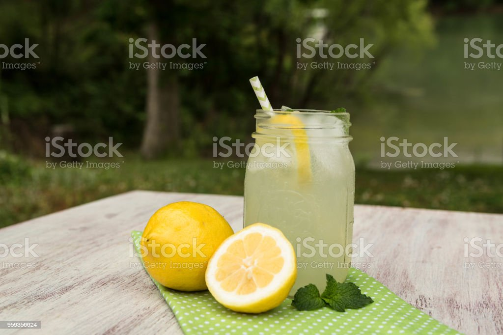 Glass Jar of Lemonade With Lemons Outside in Summer stock photo