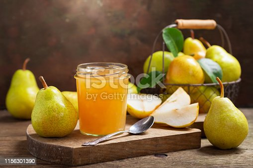 glass jar of pear jam with fresh fruits on wooden table