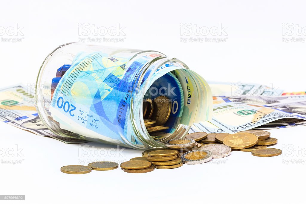 glass jar of pile of New Israeli Shekels banknotes stock photo