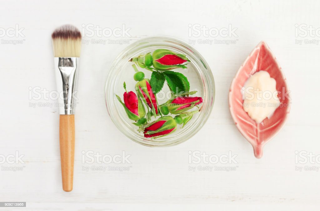 Glass jar of rose water with flowers, facial herbal mask, cosmetic application brush. stock photo