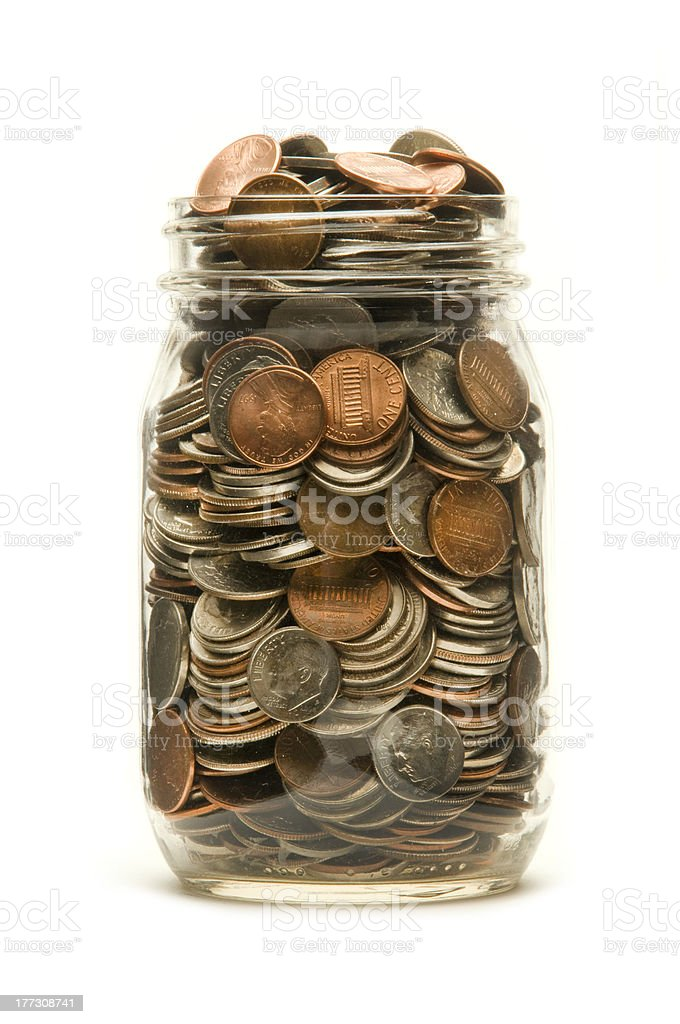 Glass jar overflowing with American coins stock photo
