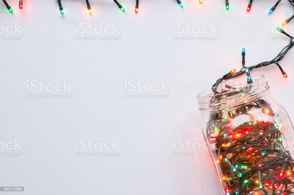 Glas mit einer glühenden Girlande Grenze Draufsicht auf weißem Hintergrund – Foto