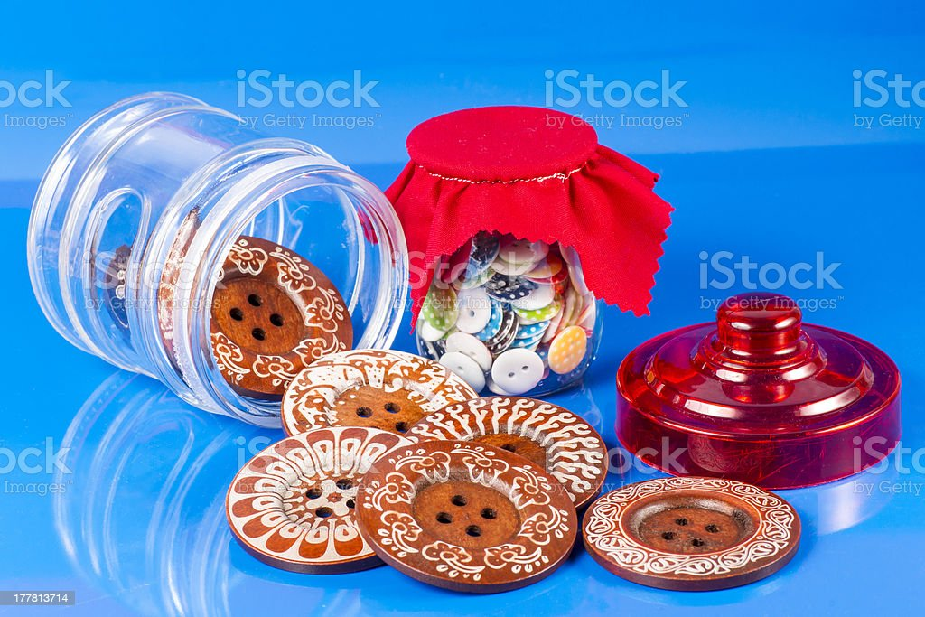 Glass Jar with Buttons on Blue. royalty-free stock photo